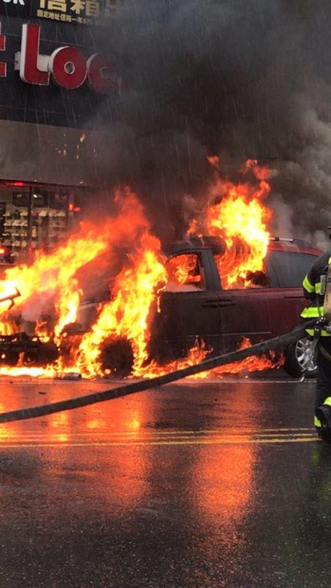 22日法拉盛鬧區街頭發生火燒車事故,嚇壞路人和周邊商家。(讀者提供)