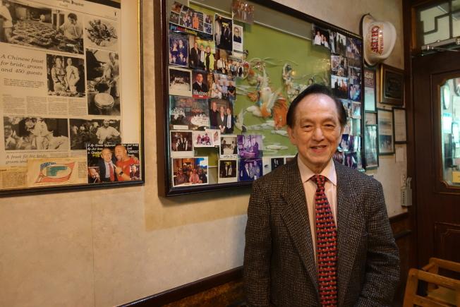 羅沛益與店內的照片墻,其中不乏名流來訪。(記者謝哲澍╱攝影)