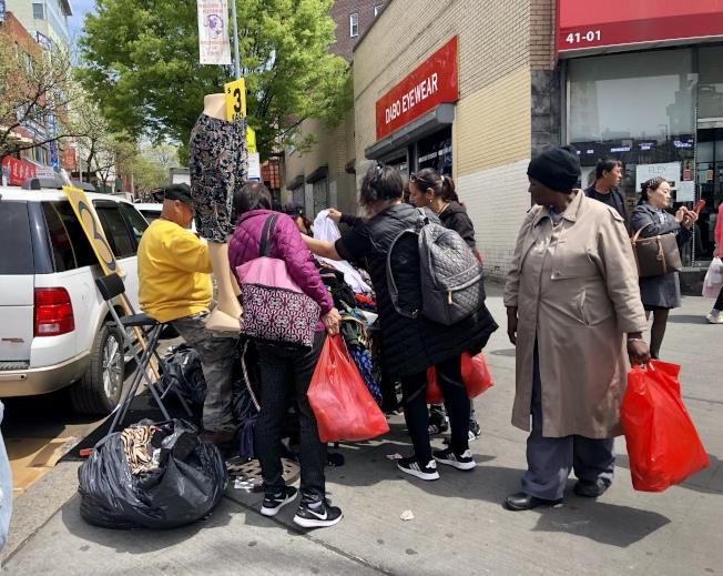 一名非華裔男子25日在屬於禁止區的緬街夾41大道上擺攤賣衣服。(記者朱蕾/攝影)