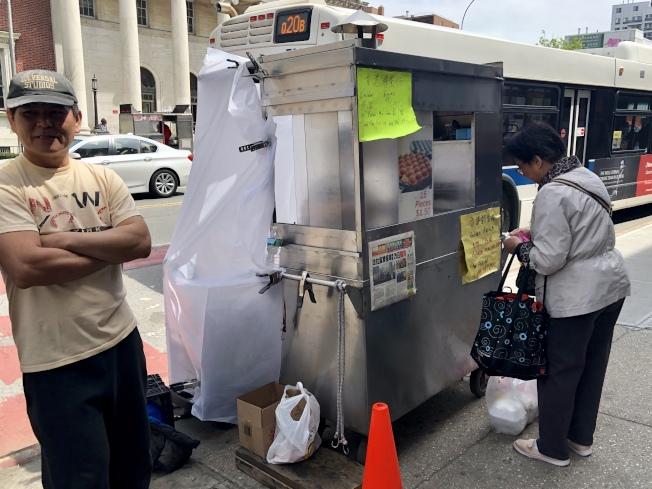 售賣香港雞蛋仔的程先生(左)把攤位移到三福大道南邊的緬街上。(記者朱蕾/攝影)