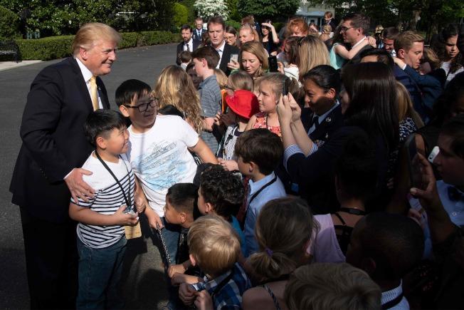 為響應「帶兒女上班日」活動,白宮職員與媒體記者25日帶著小孩到白宮,川普總統應邀與這些孩子打招呼。(Getty Images)
