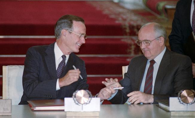 美國前總統老布希(左)與前蘇聯領導人戈巴契夫,於1991年8月 1日在莫斯科克里姆林宮簽署裁軍協定。(美聯社)