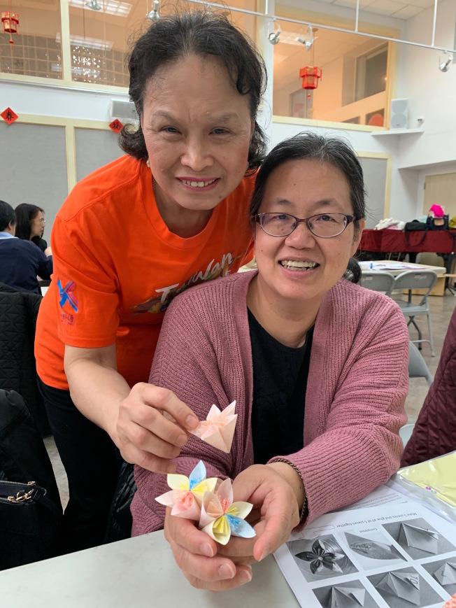許秀連(左)教導民眾製作「情竇初開」的油桐花造型摺紙。(記者賴蕙榆/攝影)