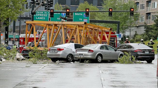 西雅圖市一棟正在施工大樓屋頂的起重機墜地後砸毀汽車,造成至少四死三傷慘劇。(美聯社)