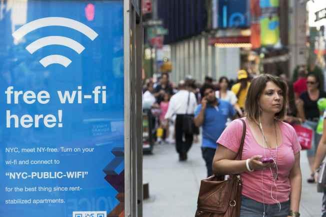 熱點搜尋軟體WiFi  Finder出現資安漏洞,建議刪除。圖為一名婦女走過紐約的WiFi電話亭。(路透資料照片)