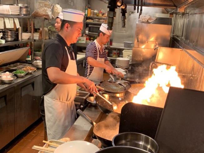 湖南土家菜辣椒王的大廚們爆炒辣味,滿屋飄香。(楊青/攝影)