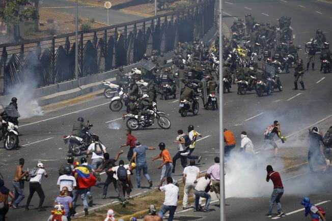 委內瑞拉反對派領袖瓜伊多30日號召民眾上街,效忠總統馬杜洛的政府出面鎮壓,圖為雙方在首都卡拉卡斯空軍基地外發生衝突。(美聯社)