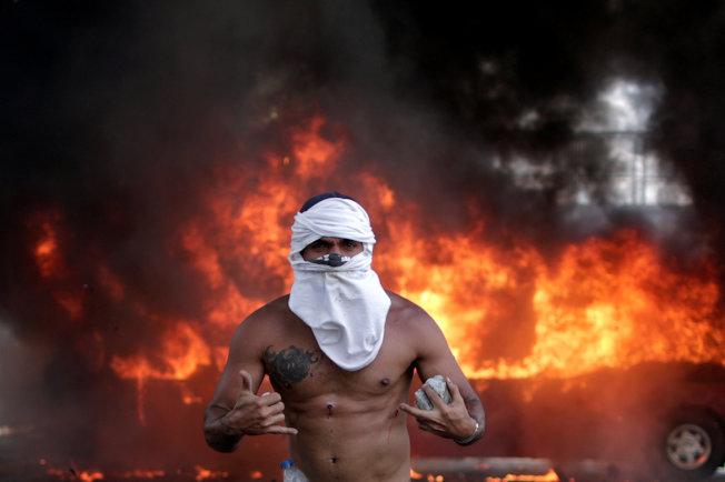 反對委內瑞拉總統馬杜洛的民眾走上街頭,與政府軍發生衝突。圖為首都卡拉卡斯一輛巴士被縱火。(路透)