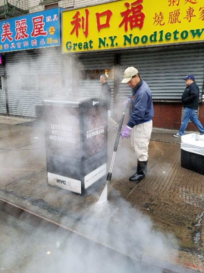 清潔人員在華埠街頭清洗「大肚子」垃圾桶。(華埠商改區提供)