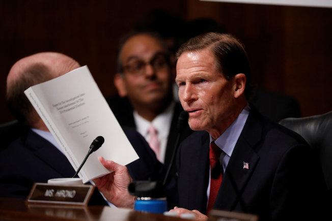 民主黨籍國會參議員布魯門索拿著厚厚一本穆勒報告,質詢司法部長巴維理。(路透)