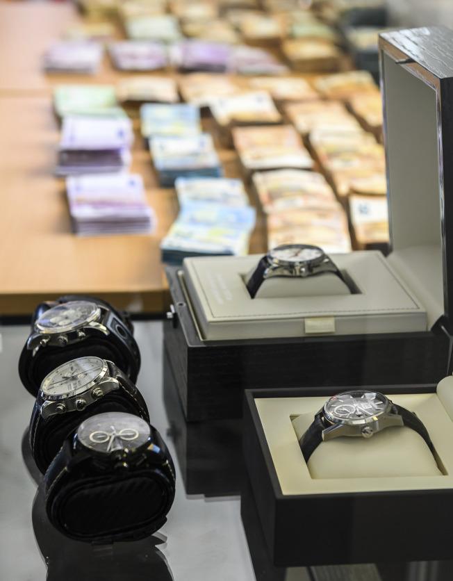 美國和歐洲警方3日宣布聯手破獲一個名為「華爾街市場」的全球最大網路黑市交易平台 。圖為查獲的鈔票和高級手表。(美聯社)