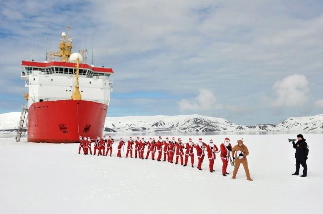 英國皇家海軍破冰船「保護者號巡邏艦」(HMS Protector)成員打扮成耶誕老人與馴鹿魯道夫假裝拉船拍照。(路透)