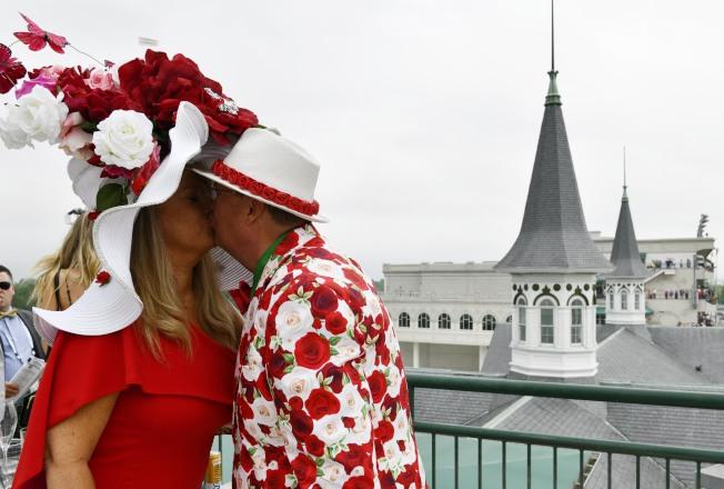 一對看賽馬的夫婦穿著與帽飾匹配的上衣,在場邊相擁親吻。(路透)
