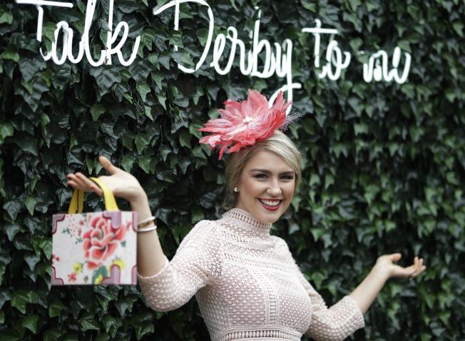時尚仕女穿戴春天的氣息,在花牆前留影。(美聯社)