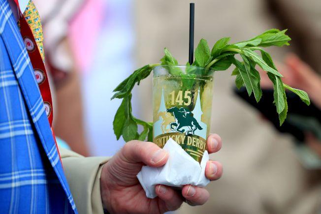 賽馬迷手捧一杯薄荷朱利酒,在場邊細啜。(Getty Images)