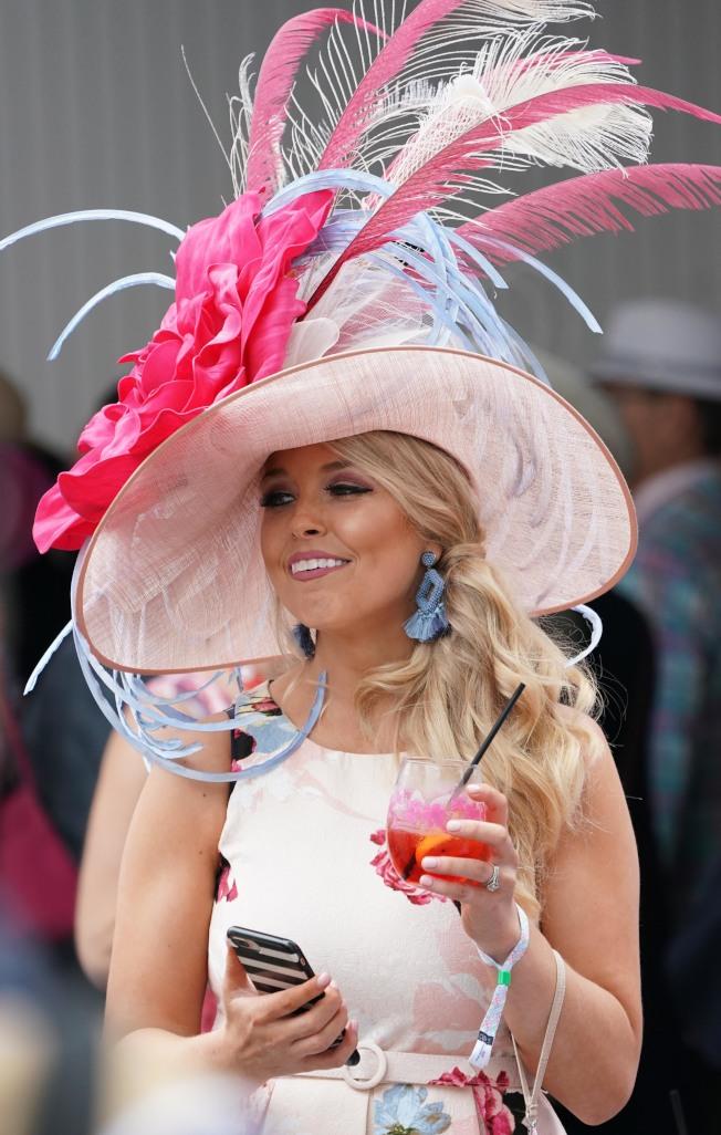 手持時髦飲料,戴著誇張的帽子,這就是肯塔基賽馬的標準配備。(路透)