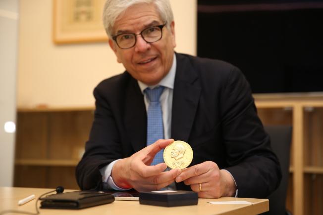 羅默展示諾貝爾獎章。(記者洪群超/攝影)