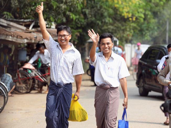 因報導緬甸政府鎮壓洛興雅人而遭緬甸政府關押一年多的路透記者瓦隆(左)及喬索歐(中),6日在仰光獲釋。(路透)