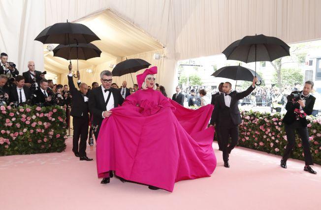 女神卡卡一襲桃紅晚禮服和誇大蝴蝶結頭飾,模仿電影「歡樂滿人間」(Mary Poppins)主角現身的方式出場。(路透)