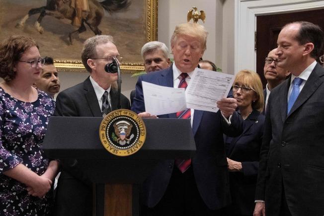 川普總統9日繼續推動降低醫療費用的政綱,要求終結「意外的醫療帳單」 。圖為川普在記者會中審視醫療帳單。(Getty Images)