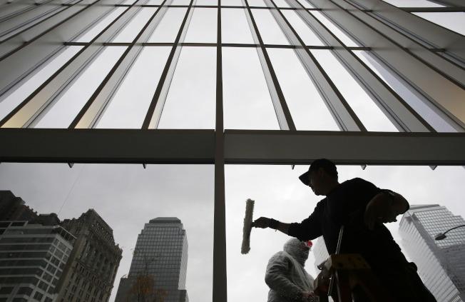 玻璃帷幕高樓在1960年代興起,員工在擦拭紐約世界貿易中心的玻璃。(美聯社)