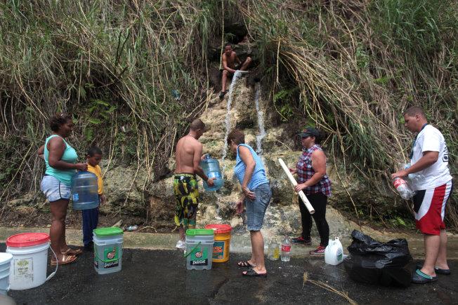 2017年秋季颶風瑪麗亞襲擊波多黎各,部分民眾無乾淨水只能取用山泉水,不少人因為這場天災成為氣候移民。(路透)