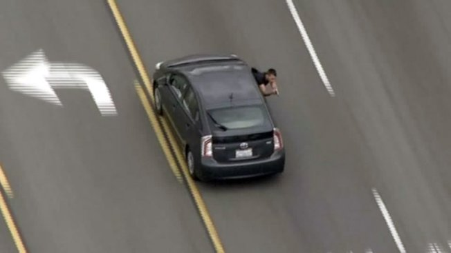 兇悍搶匪從車窗伸出上半身對警方開槍。(FOX5電視台)