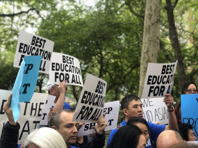 近百名家長代表手舉標語表示抗議。(記者張晨/攝影)
