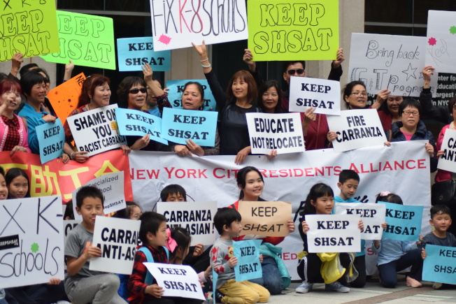華裔民眾高舉著招牌,反對市府廢除特殊高中考試。(記者顏潔恩/攝影)
