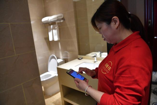 保潔員根據手機上的App接單打掃。(中新社資料照片)