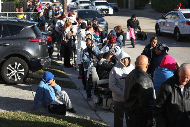 美國窮人日增,圖為佛州邁阿密居民在去年耶誕節前,排隊領取免費食物過節。(Getty Images)
