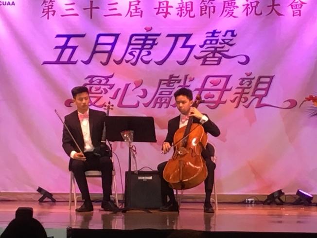 年輕人表演樂器娛樂現場母親。(記者謝雨珊/攝影)