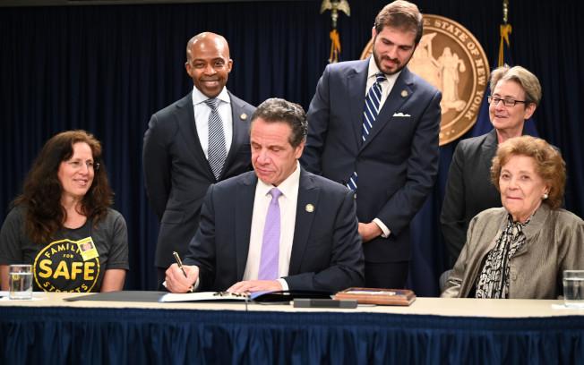 葛謨(中)12日簽字立法,將延續紐約市學校周邊路段測速攝像頭項目,並擴大攝像頭數量和監測時間。(州長辦公室提供)