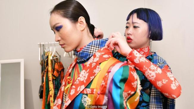 設計師裘淑婷(Qiu Shutung)在後台替模特兒整理服裝。(Getty Images)