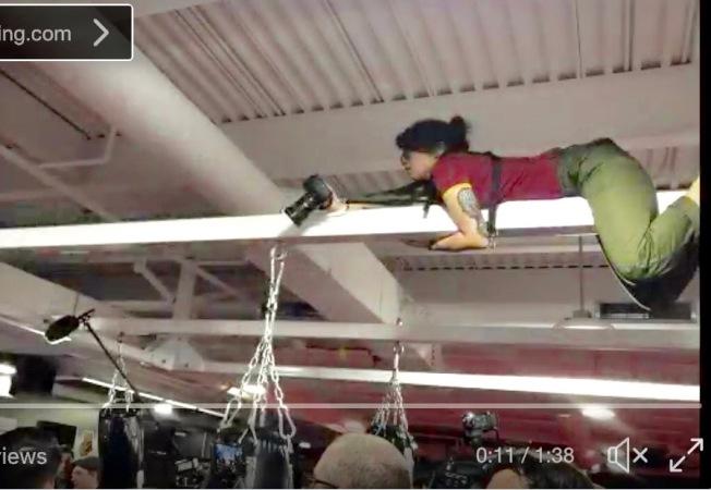 林雨翰爬上拳擊館大廳橫樑,單手拍攝混合格鬥和拳擊手Conor Anthony McGregor的訓練畫面。(楊白麗提供)