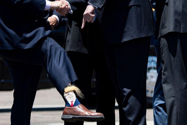 在美中貿易戰增高、伊朗情勢緊張之際,川普總統仍然按預定行程,為他的2020年大選造勢。他先在白宮對媒體就國際大事表態,然後飛到路易斯安納州從事競選活動。共和黨籍的路易斯安納州副州長努格塞(左)在機場相迎,並拉起褲管露出「川普襪」,川普頭像上還有一撮金黃色的招牌「頭髮」。(Getty Images)