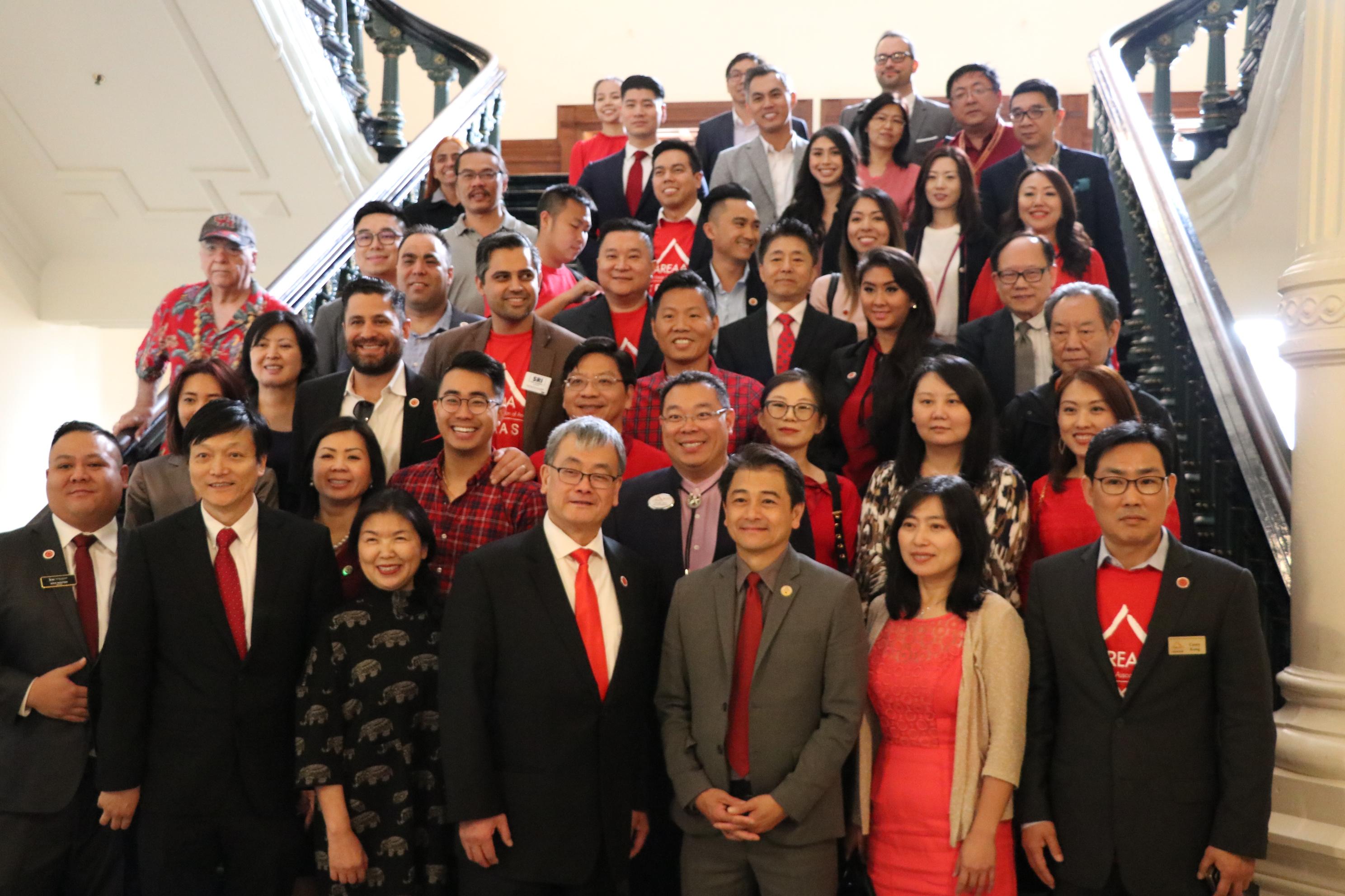 亞裔地產協會會員在德州議會迴廊樓梯上合影。