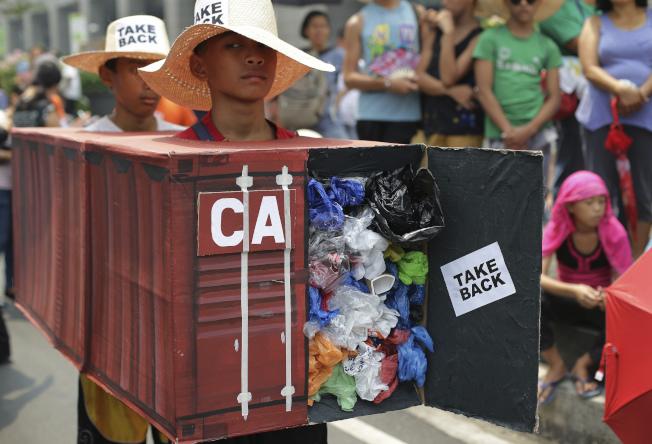 菲國環保分子扛着加拿大垃圾貨櫃模型抗議。(美聯社)