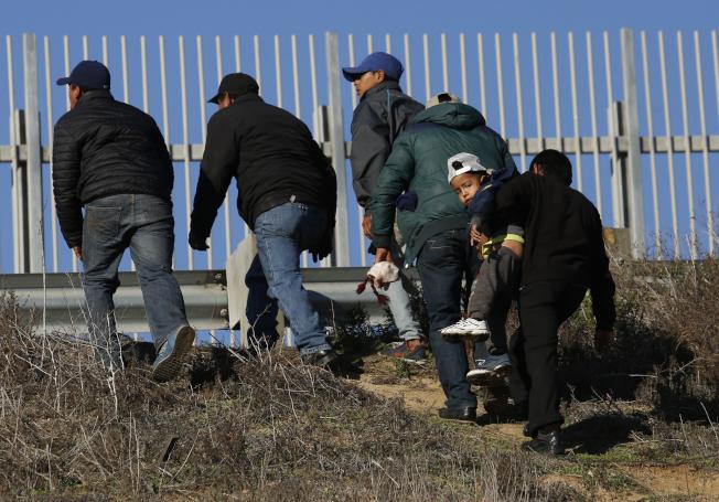 川普總統要移民進入美國之前得通過「公民常識測驗」,引發爭議。圖為宏都拉斯無證移民從墨西哥提璜納翻越美墨邊界圍欄,進入美國。(美聯社)