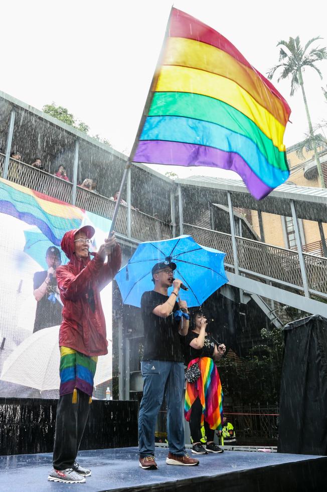 中華民國立法院17日三讀通過同婚專法,成為亞洲第一個同婚合法化的國家,同志先行者祁家威(左)開心的揮舞彩虹旗。(記者葉信菉/攝影)