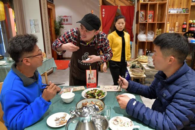 「無聲餐廳」服務員用手語詢問顧客是否需要米飯。(新華社)