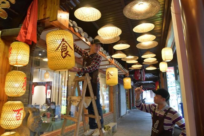 「無聲餐廳」店員在店外的走廊上懸挂裝飾用的燈籠。(新華社)
