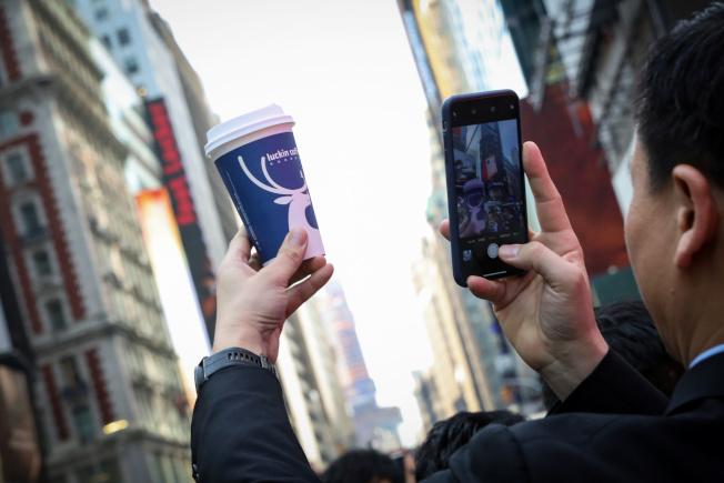 瑞幸咖啡高管在公司首次公開募股時在紐約納斯達克市場現場拍攝了Luckin Coffee杯。(路透)