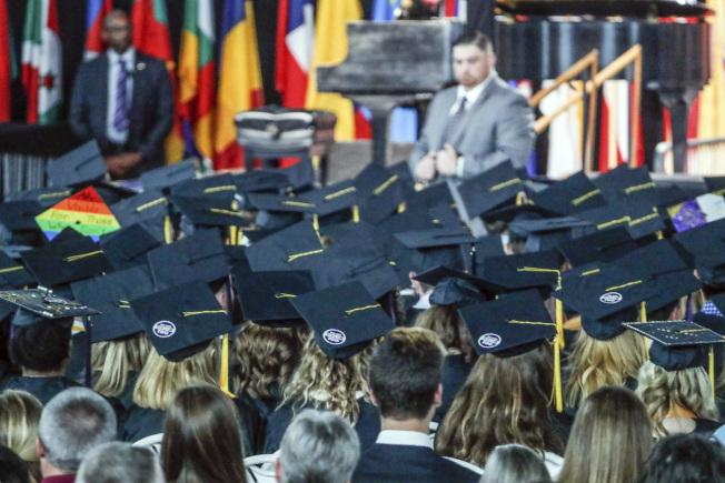 副總統潘斯應邀出席印第安納州泰勒大學畢業典禮,在演講時推銷川普政績,引起部分師生退席抗議。圖為部分畢業生在帽子貼上「我們也是泰勒」字樣。(美聯社)
