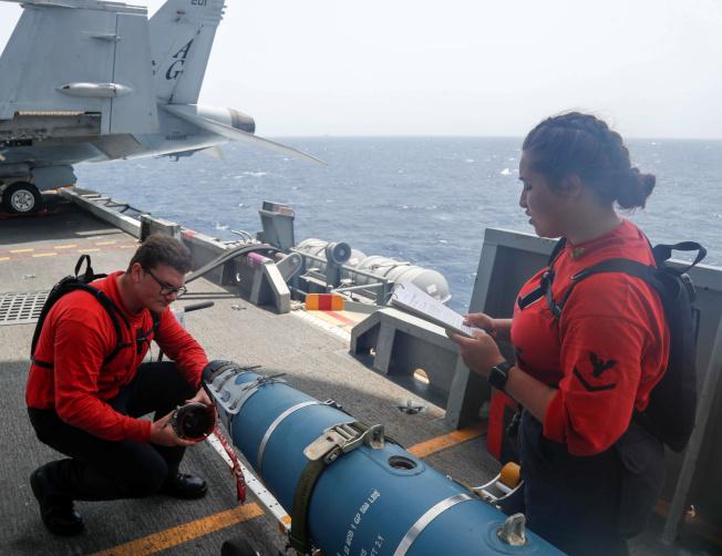 圖為美國航母林肯號人員檢查飛彈設施。(路透)