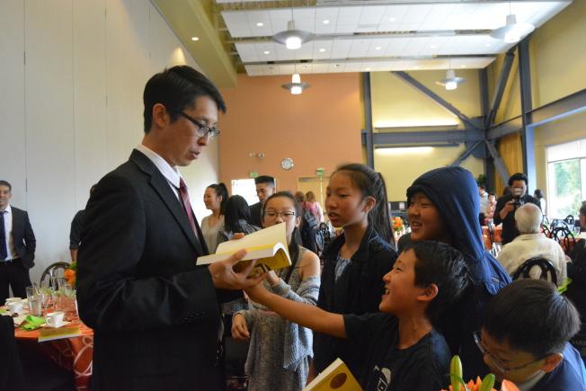 楊謹倫在東灣州大舉行的午宴上簽名贈送成名作「美生華人」。(記者劉先進/攝影)