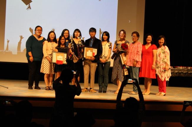 三位畢業生林卉妮(左三)、李佳駿(中)與夏幼娜(右四)與母親、老師及學校成員們合影。右一為林香蘭,左一起為夏忠菁、傅瑾玲。(記者林昱瑄/攝影)