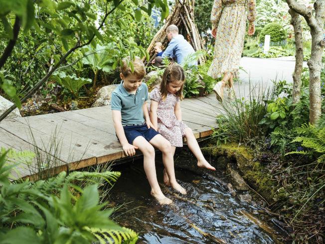 喬治與夏綠蒂光著腳丫在小溪邊嬉戲。(美聯社)