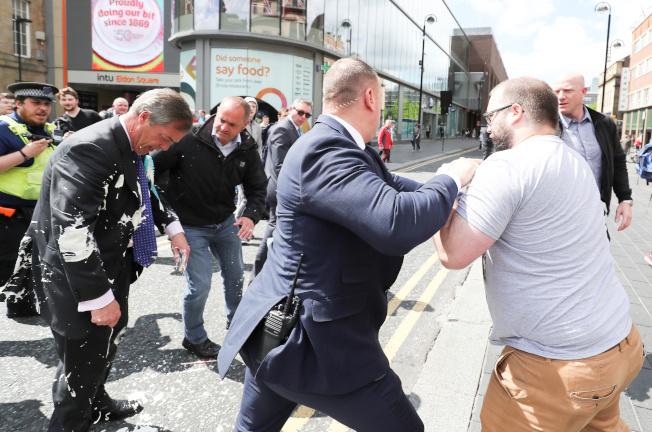 英國脫歐黨黨魁法拉吉(左)20日輔選時慘遭奶昔攻擊,狼狽非常。(路透)