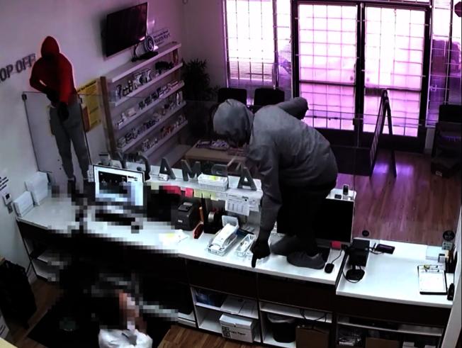 在警方公布的錄像中,有兩名男子跳過櫃檯搶劫。(視頻截圖)